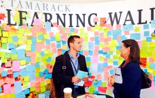 Nathan Graeser, left, and Lisa Anderson, co-chair of the career advancement working group, discuss strategies during the Collective Impact Summit in Vancouver, Canada.